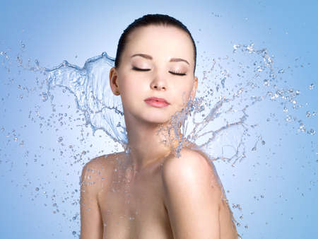 Beautiful portrait of  woman with fresh skin in splashes of water - blue background photo