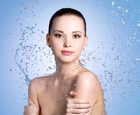 Splashes of water on the beautiful young woman with clean fresh skin - colored background photo