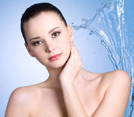 Sensuality young woman with stream of water - blue background photo