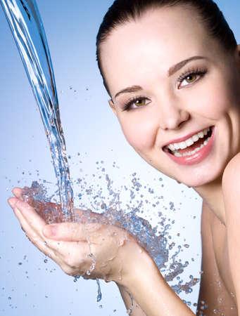 woman in water: Happy laughing woman washing face - studio shot
