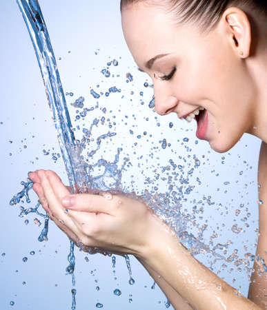 water stream: Young woman washing face under the stream of water - blue background
