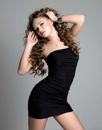 Glamour beautiful sexy woman with long hair dancing in black dress - grey background photo