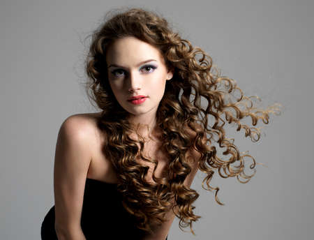 Portrait of glamour beautiful young woman with long curly hair photo