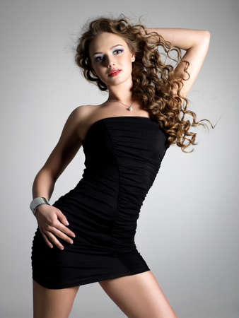 Glamour and beauty of young attractive stylish woman with long hairs in elegant dress - vertical photo