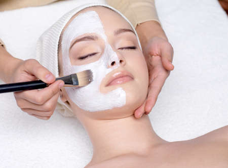 Beautiful young woman having a facial cosmetic mask at spa salon