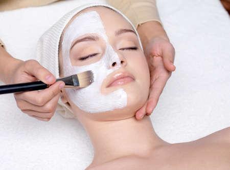 ansikts: Vacker ung kvinna att ha en ansiktsbehandling kosmetisk mask på spa salong