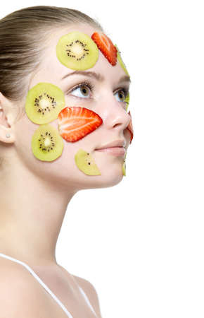 Young beautiful girl in profile with fruit mask on her face - white background photo