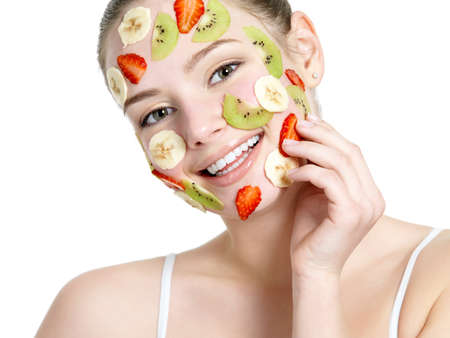 Beautiful young smiling cheerful womanwith fruit mask on her face - isolated on white background photo