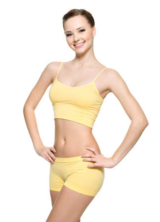 Happy young woman with beautiful slim body in yellow sport clothes -  isolated on white background  photo