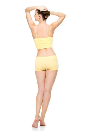 Back view of a beautiful sporty female body in yellow underwear posing isolated on white background photo