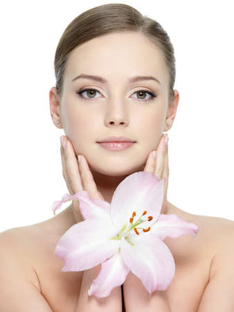 Portrait of beautiful girl with lily near her pretty face with clean skin - vertical Stock Photo - 12349750