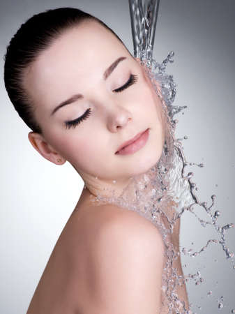 Clean water falling on the beautiful face of woman - studio shot photo
