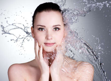 Spatten van water op de prachtige gezicht van de jonge vrouw - grijze achtergrond Stockfoto