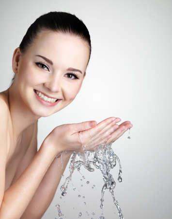 lavandose las manos: Hermosa mujer sonriente joven lavando la cara con agua - estudio de disparo Foto de archivo