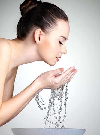 gezicht: Portret van een jonge vrouw haar gezicht wassen met schoon water - studio Stockfoto