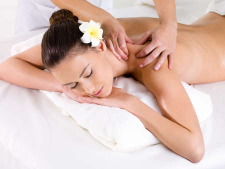 massage therapy: Woman in beauty salon having massage of shoulder   - horizontal