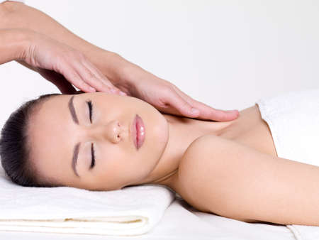by hand: Massage for the face and neck of young beautiful woman in spa salon - close-up portrait Stock Photo