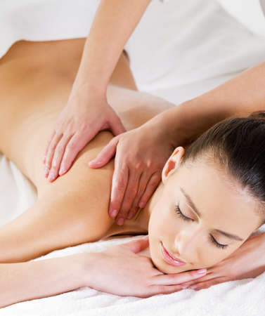 massage: Woman relaxing on the salon and having massage on her shoulder - vertical