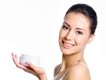 rejuvenate: Close-up portait of happy young beautiful woman holding moisturizing facial cream - isolated on white