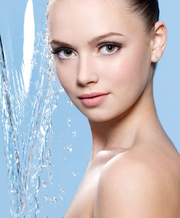 Portrait of beautiful young woman with stream of water - blue background photo