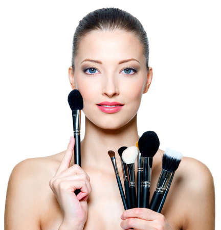 Portrait of the beautiful woman with make-up brushes near attractive face. Adult girll posing over white background photo