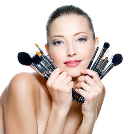 atractive: Beautiful young adult woman  holds the make-up brushes near atractive face. Fashion  model posing over white background