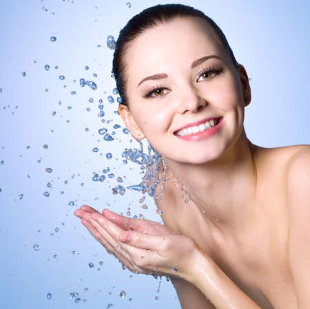 Healthy smiling  woman washing her face with clean water photo