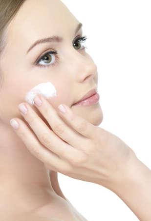 La aplicación de crema facial en la mejilla de la joven y bella mujer - aislados
