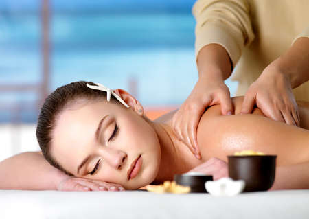 salon and spa: Young beautiful relaxing woman getting spa massage of shoulder in beauty salon - nature background.  Stock Photo