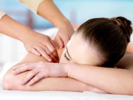 salon de belleza: Joven mujer de relax en el sal�n de belleza y hacer masaje en los hombros - fondo de color