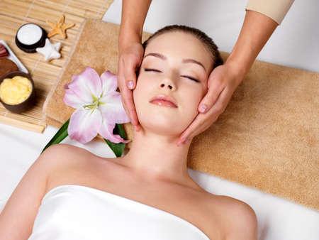 뷰티 살롱에서의 얼굴에 그녀의 피부를위한 안마를 갖는 휴식 아름다운 여자 - 수평 스톡 콘텐츠