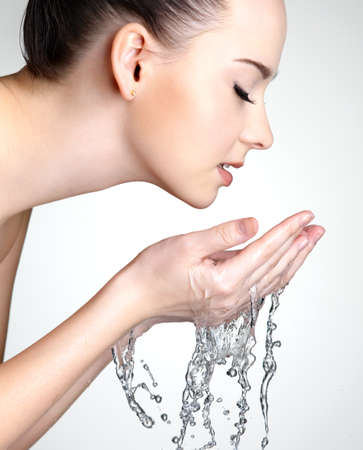 Profile portrait of beautiful woman washing  face with  water - studio photo