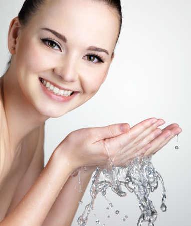 vertical wellness: Beautiful smiling woman washing her face with water - studio shot