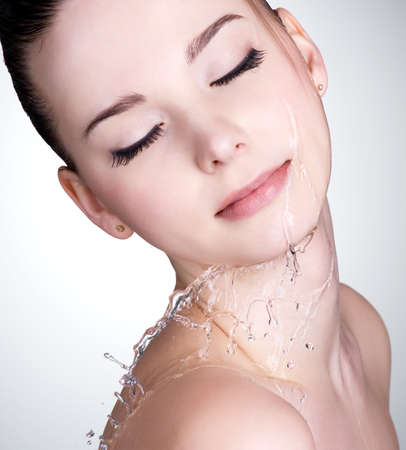 Close-up portrait of young woman with drops of water on her beautiful face Stock Photo - 12460924