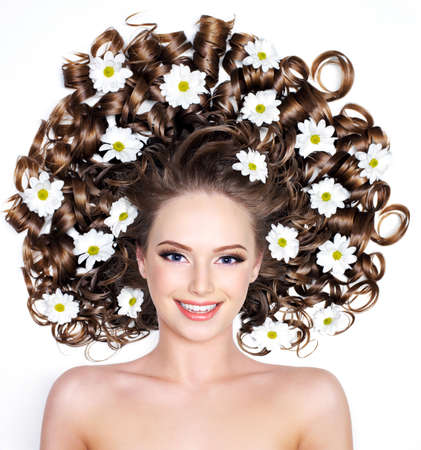 long curly hair: Smiling young woman with flowers in long hair - white background