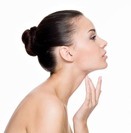 piel morena: Hermosa mujer cuida de la piel del cuello, posando en el estudio aislado en blanco Foto de archivo
