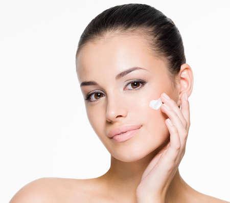 mimos: Retrato de la mujer hermosa que aplica la crema en la cara - aislados en blanco Foto de archivo