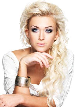 Bella donna bionda con lunghi capelli ricci e trucco stile. Ragazza in posa su sfondo bianco photo