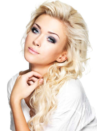 Beautiful blond woman with long curly hair and style makeup. Girl posing on white background photo