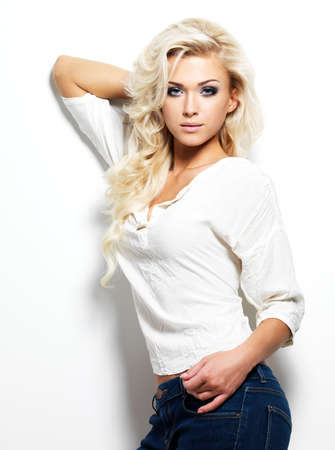 Fashion model woman with long blonde hair posing in studio.  photo