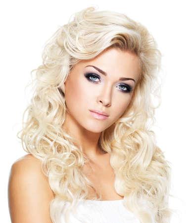Belle femme avec de longs cheveux blonds boucl�s. Portrait de mannequin avec maquillage lumineux. Isol� sur fond blanc photo