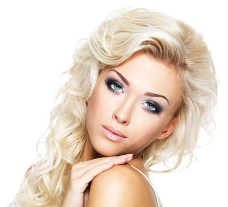Beautiful blond woman with long curly hair. Fashion model with bright makeup - isolated on white photo