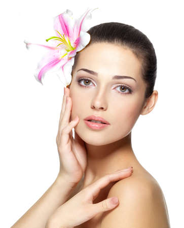gezicht: Schoonheid gezicht van de jonge vrouw met bloem. Schoonheidsbehandelingen concept. Portret op witte achtergrond Stockfoto