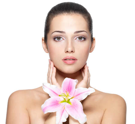 Beauty face of young woman with flower. Beauty treatment concept. Portrait over white background photo