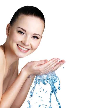 manos limpias: Hermosa mujer sonriente joven lavando la cara con agua - estudio de disparo Foto de archivo