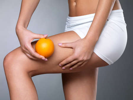 with orange and white body: Female squeezes cellulite skin on her legs - close-up shot on white background