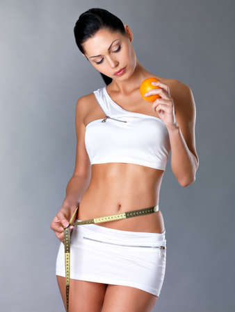 cocnept: Girl measures figure with a measuring tape and holding the orange. Healthy lifestyle cocnept. Stock Photo