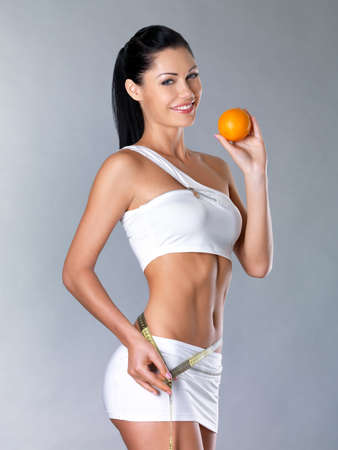 with orange and white body: Smiling girl measures figure with a measuring tape and holding the orange. Healthy lifestyle cocnept.