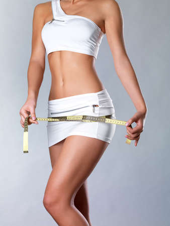 Girl measures thigh with a measuring type. Healthy lifestyle cocnept. photo