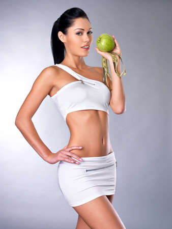 Portrait of a healthy woman with apple and bottle of water. Healthy fitness and eating lifestyle concept.  photo